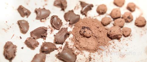 Proces lepienia trufli czekoladowych na kuchennym blacie.