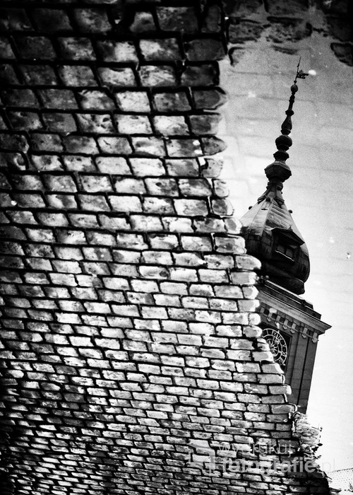 Odbicie Zamku Królewskiego w kałuży przy ulicy Świętojańskiej. Typowy, chłodny poranek na warszawskim Starym Mieście.
