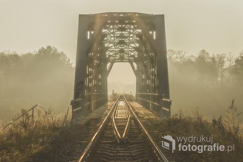Kolejna fotografia mostu kolejowego nad rzeką Brok. Słońce było już dosyć wysoko. Wykorzystałem sytuację, kiedy wyszło centralnie nad samą konstrukcję mostu i rozświetliło ją swoimi promieniami. Nad wodą unosiła się lekka mgła dopełniając tajemniczość sceny.