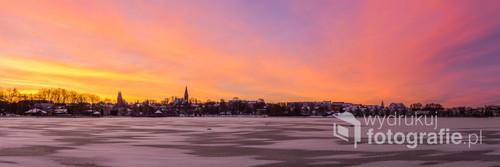 Niezwykle kolorowy zimowy wschód Słońca w Ostródzie. Panorama przedstawia widok z brzegu Jeziora Drwęckiego na centrum miasta.