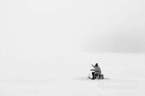Samotny wędkarz na Jeziorze Sajmino otoczony przez mgłę.