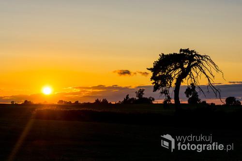 Zmierzające ku zachodowi Słońce uchwycone we wsi Nastajki, niedaleko Ostródy.