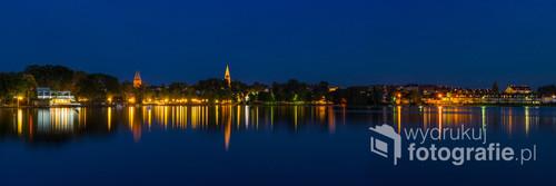 Nocny widok na zatokę Jeziora Drwęckiego z charakterystycznymi wieżami dwóch kościołów.