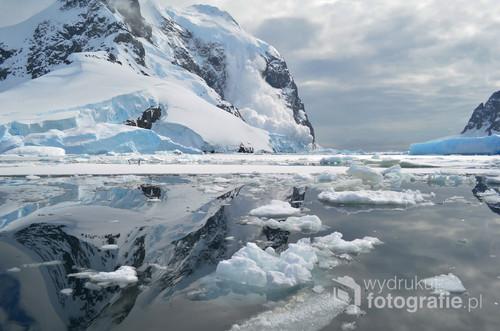 Zdjęcie zostało wykonane podczas wyprawy na Antarktydę z poziomu pontonu. Mimo że początkowo celem było uchwycenie dwóch pingwinów znajdujących się na krze, ostatecznie zdjęcie zawdzięcza swoją wyjątkowość spadającej lawinie, której towarzyszył ogromny hałas. Zaledwie kilkadziesiąt metrów od miejsca, w którym spadła lawina znajdowali się moi przyjaciele w kajakach. Całe szczęście nikomu nic się nie stało.