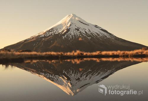 Zdjęcie przedstawia górę Taranaki znajdującą się na wyspie Północnej w Nowej Zelandii. Zdjęcie zrobione 23 września o wschodzie Słońca, padające więc promienie są pierwszymi wiosennymi promieniami w Nowej Zelandii.