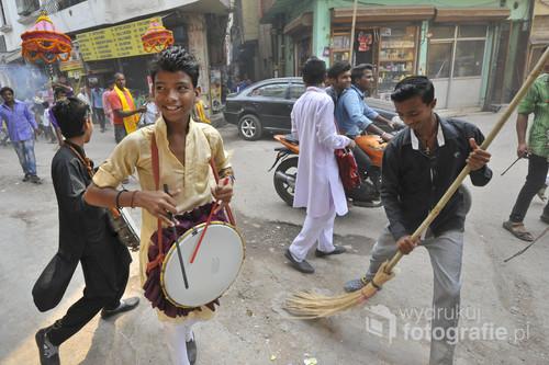 Dzielnica Paharganj w New Delhi.  W Indiach życie toczy się na ulicy. Rozbawieni chłopcy grają na różnych instrumentach, bawią się, tańczą i śpiewają.  Parada kolorów, zapachów i dźwięków.  Zdjęcie nagrodzone zostało Grand Prix konkursu fotograficznego Fotoglob podczas festiwalu podróżniczego KOLOSY w Gdyni w 2015r.