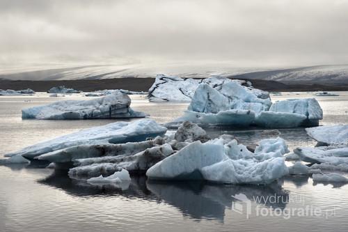 Wielobarwne góry lodowe na islandzkim jeziorze Jokursarlon. Lodowe bryły i niezwykłe arktyczne światło tworzą magiczną atmosferę tego miejsca.