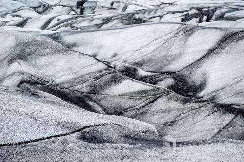 Abstrakcyjne zdjęcie lodowca na Islandii przypomina grafikę wykonaną węglem. Zdjęcie to zdobyło Złote Szkło w kategorii Natura na Otwartych Mistrzostwach Fotograficznych.