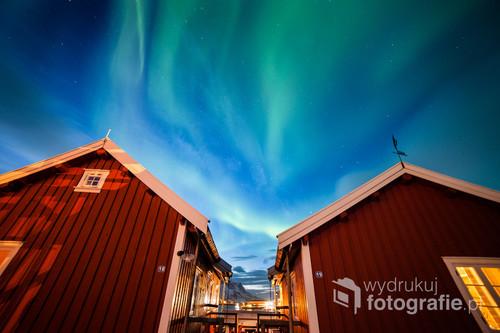 Wioska Reine na norweskich Lofotach. Malownicze czerwone domki kontrastują z zielono-niebieskim niebem, na którym tańczy zorza polarna.