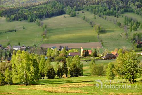 Ujrzałem taki widok, wychodząc ze szlaku w lesie. Majowe słońce pięknie podkreśliło urokliwe położenie wsi. Stary Gierałtów, Góry Złote, Dolny Śląsk. Zdjęcie wykonane w maju 2020r.