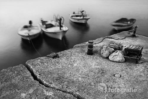 Fotografia powstała na jednym z wybrzeży czarnogórskich na Adriatyku. Ulotność ludzkiego życia symbolizują łodzie, a trwałość ziemi. Praca pochodzi z cyklu