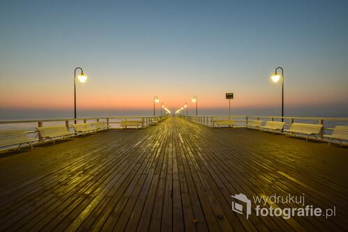 Fotografia przedstawia molo w Gdyni Orłowie tuż przed wschodem słońca.