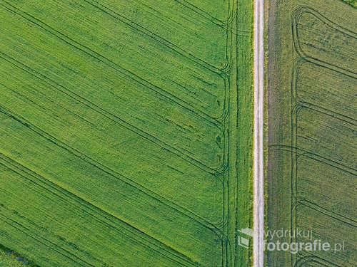 Fotografia pola oraz wiejskiej drogi z perspektywy drona.