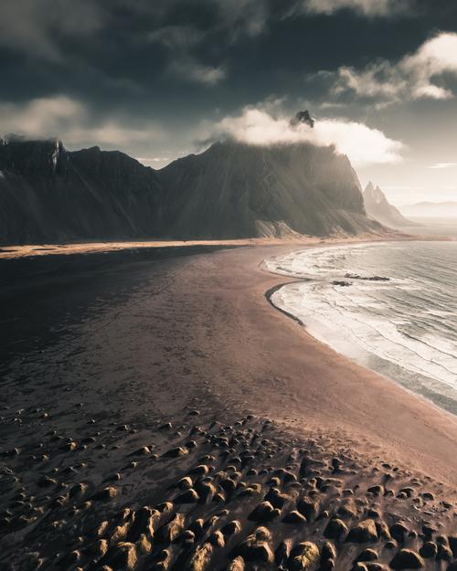 Zdjęcie przedstawia przepiękny krajobraz Islandii o wschodzie Słońca. Góra Vestrahorn, czarna plaża i naturalnie wyrastające garby porośnięte trawą to wyjątkowa kompozycja.