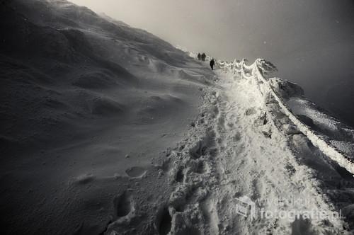 Zdjęcie to zrobiłem podczas mojego pierwszego wejścia na Śnieżkę pod koniec listopada 2013.  Góra ta jest bardzo popularna zarówno latem i zimą,  jest ona jednak bardzo kapryśna. Znana jest z silnych wiatrów. Kilka dni wcześniej zamieć zasypała szlak oraz łańcuchy.  Zdjęcie zrobiłem Pentaxem K5 z SMC-DA 15mm/4