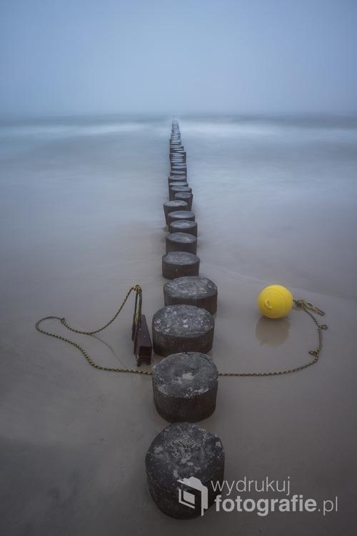 Fotografię wykonałem w czerwcu w Ustce, podczas jedynego mglistego dnia tamtego miesiąca. Tuż obok falochronu znajduję się żółta bojka, która służy ratownikom morskim do wyznaczania granic kąpieliska. Ustka, PL  Fotografia wyróżniona w międzynarodowym konkursie fotograficznym