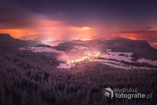 Piękna i mroźna noc na Szczelińcu Wielkim, lekkie chmury które wspaniale odbijają światła pobliskich miejscowości i wiosek, niesamowity efekt. Po lewej stronie zdjęcia widać kawałek Błędnych Skał, po środku Pasterka a po prawej stronie szczyt Koruna w Czechach