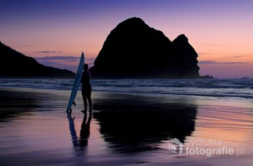 Surfer o zachodzie słońca na plaży Piha w Nowej Zelandii. Plaża ta jest idealna do surfingu a fale osiągają tam spore wysokości.