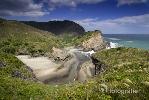 Piha Beach. Plaża niedaleko Auckland w Nowej Zelandii. Na plażę przyjeżdża mnóstwo surferów gdyż są tam idealne warunki do tego sportu. Bardzo rozległa, piaszczysta ze skałą po środku o nazwie Lion Rock.