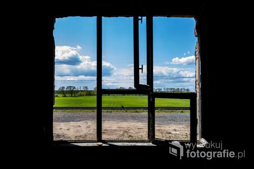 Zdjęcie zrobione w opuszczonej fabryce z widokiem na piękne pole oraz tory kolejowe.