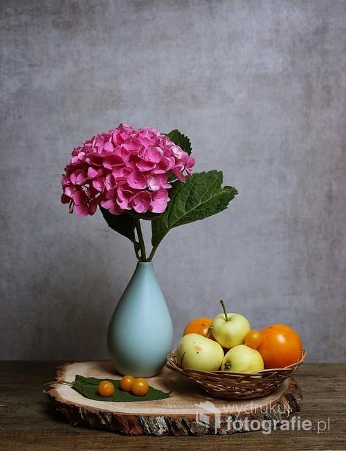 obraz martwej natury z hortensją w niebieskim wazoniku obok jabłka i mirabelki