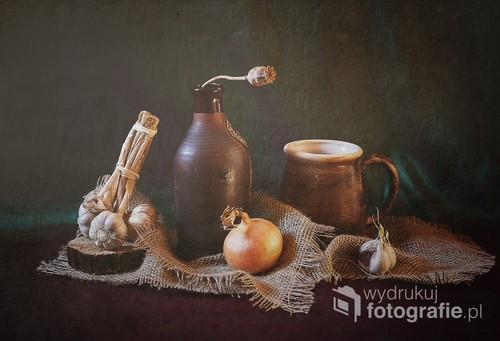 martwa natura z czosnkiem i cebulą w otoczeniu glinianych naczyń