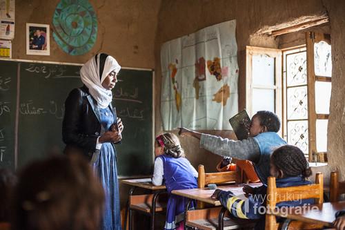 """Miejscowość  Khamlia położona jest 50 km od granicy z Algierią. Większość ludzi zamieszkujących wioskę ma czarny kolor skóry, dlatego jej lokalna nazwa to """" Czarna Wioska"""". Poziom edukacji w tym rejonie jest bardzo niski. Kilka lat temu powstała tam niewielka szkoła sfinansowana przez Hiszpan.  Na lekcję odbywające się raz w tygodniu, przychodzą dzieci w różnym wieku. Miejscowi nauczyciele pracują tam za darmo."""