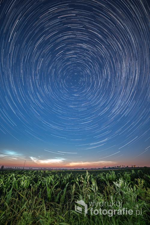 Fotografia pozornego ruchu gwiazd, zarejestrowanego podczas 65-minutowego naświetlania. W samym centrum kręgów znajduje się Gwiazda Północna - aparat był skierowany dokładnie na północ, dzięki czemu udało się uzyskać idealną symetrię zdjęcia.  Ta symetria została nieco przełamana przez obłoki srebrzyste, widoczne nad horyzontem. Zdjęcie pochodzi z 16. czerwca 2020 roku.