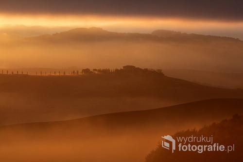Świt w Val d'Orcia: słońce prześwitujące przez mgłę i chmury zanurzyło krajobraz w ciepłych barwach.