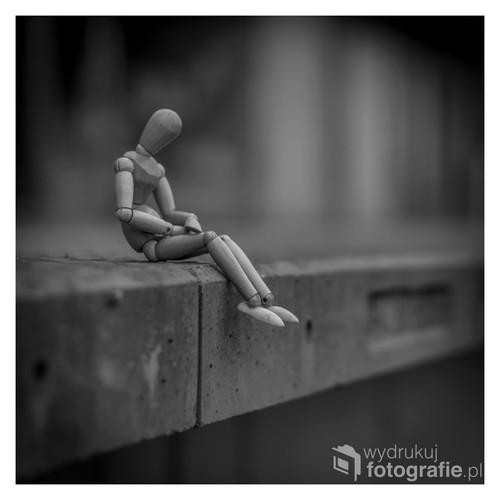 fotografia przedstawia drewnianą postać o wysokości ok. 14cm, zdjęcie zostało wykonane na jednym z peronów pod Poznaniem. Po wykonaniu fotografii została ona poddana obróbce w programie graficznym