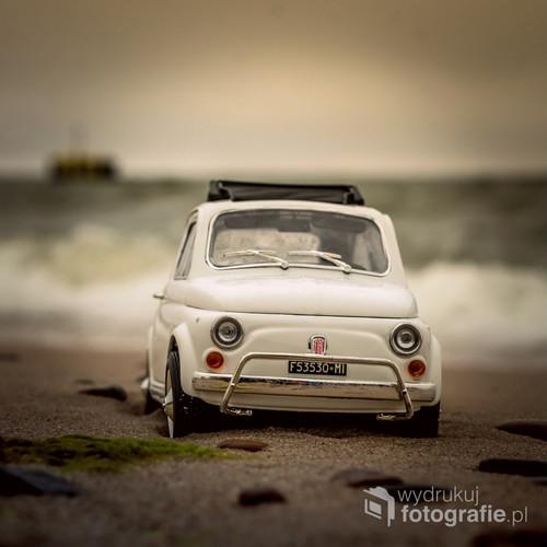 fotografia została wykonana na plaży w Chłopach, przedstawia ona model Fiata 500 w skali 1:18, w tle widać morze oraz urządzenie do ściągania z plaży kutrów rybackich, które wypływają na połowy