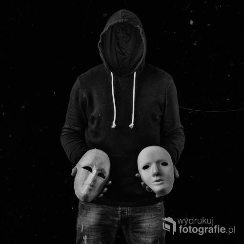 fotografia przedstawia postać trzymającą dwie maski, efekt