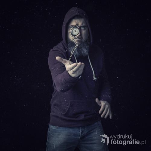 fotografia przedstawia postać podrzucającą zegarek... być może jest to współczesny zegarmistrz ;)
