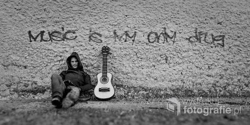 fotografia przedstawia model/figurkę człowieka oraz gitary. napis został dodany w programie graficznym.