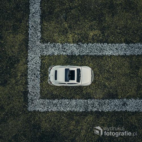 fotografia przedstawia model fiata 500 położonego na boisku do koszykówki.