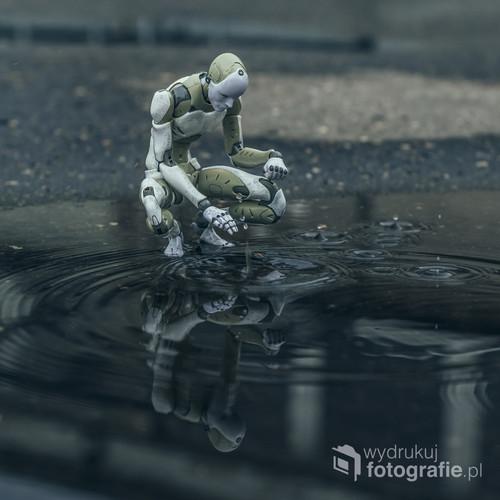 fotografia wykonana przy pomocy figurki przedstawiającej robota po krótkich ale obwitych opadach deszczu.