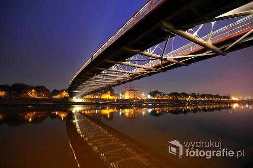 Kraków- Podgórze. Znana i lubiana kładka zawieszona nad spokojnym lustrem rzeki.