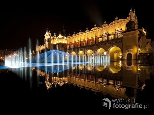 Krakowskie Sukiennice odbite w mokrej granitowej płycie fontanny, która miała swego czasu tylu zwolenników co wrogów. Zdjęcie wykonane przy pomocy szerokiego obiektywu 10 mm. Fotografia opublikowana na portalu 1x.com