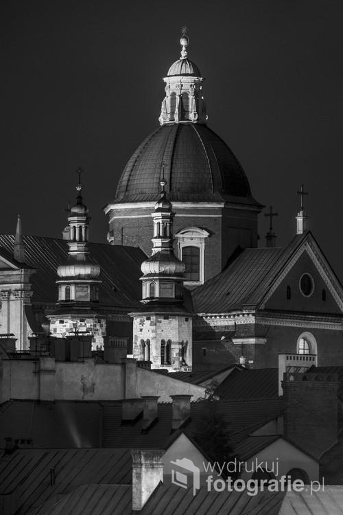 Nocna fotografia cyfrowa wykonana w lutym 2018 r.. Przedstawia widok ze wzgórza Wawelskiego na kopułę Kościoła Św. Apostołów Piotra i Pawła, dwie wierze Kościoła św. Andrzeja i dachy pobliskich kamienic.