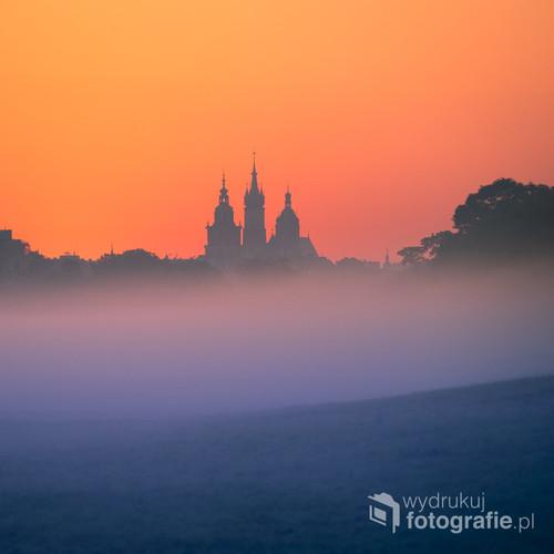 Zdjęcie wykonane w mglisty poranek z krakowskich Błoń. Przedstawia niesamowitą kompozycję kolorów utworzoną przez jeszcze nieoświetloną mgłę na krakowskich Błoniach i już rozświetlone niebo, które jest doskonałym tłem dla sylwetek wierzy ratuszowej i wierz kościoła Mariackiego.