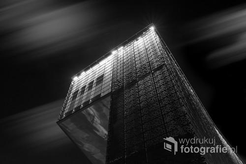 Fotografia cyfrowa, przedstawia budynek Cricoteki w Krakowie na tle nocnego nieba z przesuwającymi się chmurami.