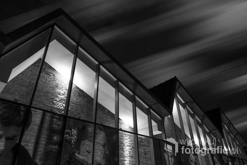 Fotografia cyfrowa, przedstawia budynek MOCAK (Muzeum Sztuki Współczesnej) w Krakowie na tle nocnego nieba z przesuwającymi się chmurami.