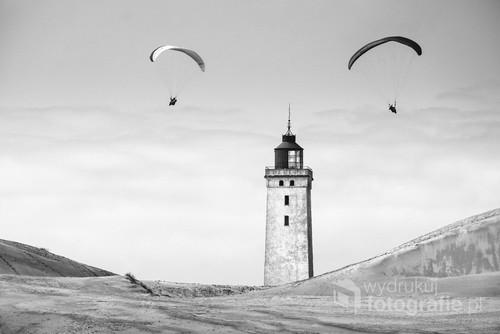 Fotografia cyfrowa wykonana w Jutlandii. Przedstawia latarnie morską Rubjerg Knude w otoczeniu paralotniarzy. Za kilka lat latarnia podobnie jak muzeum i kawiarnia, znikną pod powierzchnią piasku przesuwającej się wydmy