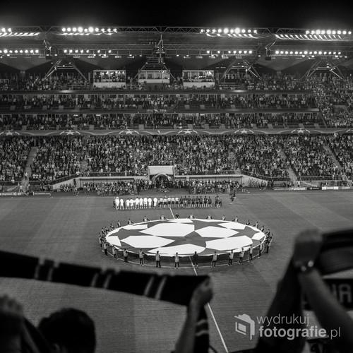 Zdjęcie wykonane z trybuny wschodniej im Kazimierza Deyny podczas pierwszego po 20 latach meczu Ligi Mistrzów na stadionie Wojska Polskiego przy ulicy Łazienkowskiej 3. Właśnie odgrywany jest hymn UEFA Champions League, jednak na stadionie dominuje przeraźliwie głośny śpiew kibiców. Zdjęcie wykonane średnioformatowym aparatem Yashica Mat 124G, na materiale światłoczułym Ilford Delta 100, wywołanym i zeskanowanym w domowej ciemni.