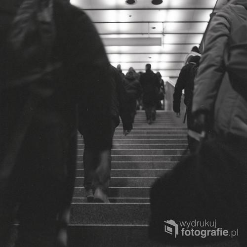 Bezimienny tłum pokonuje przedostatnią przeszkodę do celu, którym jest dom. Zdjęcie wykonane aparatem analogowym Yashica Mat 124G na profesjonalnym filmie Ilford Delta 400. Warszawa, styczeń 2013.