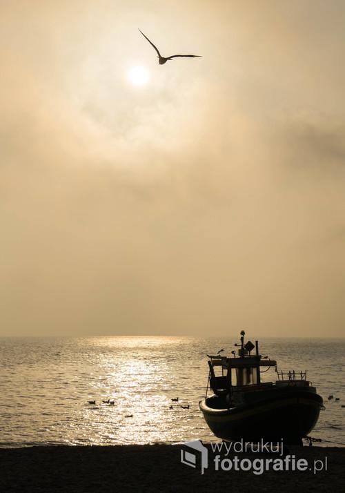 Jedno z najbardziej charakterystycznych miejsc nad Bałtykiem to plaża w Gdyni Orłowo z kutrami rybackimi. Jeden z nich jest na zdjęciu, za nim pięknie oświetlone morze z mewami śmieszkami.