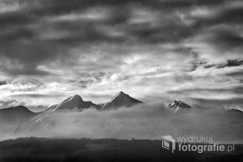 Ośnieżone szczyty Tatr Bielskich przedzierające się przez chmury. Zdjęcie zostało wykonane w styczniu 2019 roku z Łapszanki.