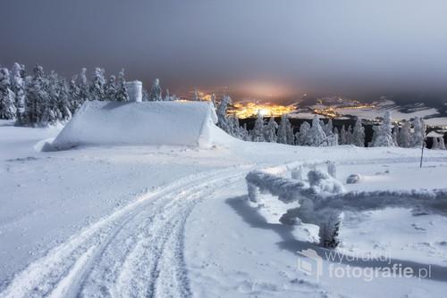 Zimowy, górski krajobraz z widokiem na miasto nocą. Zdjęcie zostało wykonane w Czeskich Jesenikach, przy schronisku na Seraku  Zdjęcie zostało wyróżnione w magazynie A-Z Top Photo Magaziny