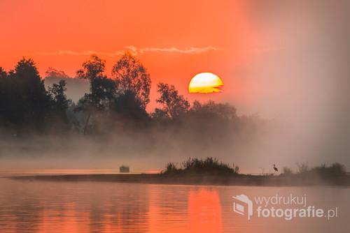 Wczesny lipcowy poranek nad Bugiem. Słonce wstaje, czapla poluje na wysepce, słonce wolno podnosi sie , a mgła szybko nadciąga z parwej strony. Po chwili nie widać już ani czapli, ani słońca.