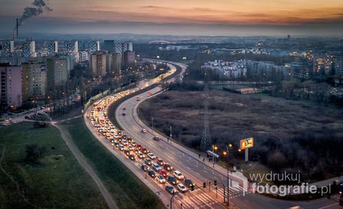 Fotografia przedstawia godziny szczytu w Krakowie. Zachodzące słońce wraz ze wzmożonym ruchem ulicznym oraz działającą w tle elektrociepłownią tworzą niesamowity klimat.